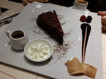 Extremely rich Nutella cake with additional chocolate sauce and whipped cream